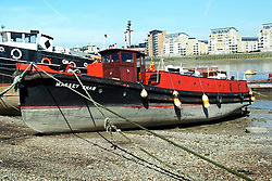 © Licensed to London News Pictures. 13/12/2013. Massey Shaw on exposed foreshore at Greenwich prior to restoration, , used with permission of the Massey Shaw Trust.The famous and historic fireboat MASSEY SHAW has returned to London today after a Heritage Lottery funded restoration. The fireboat was built in the 1930s and played a role in the war, helping to evactuate soldiers from Dunkirk and also dealing with fires from the river during the Blitz. The restoration of Massey Shaw was carried out in Gloucester after a lottery award in 2008. She is the oldest operating fireboat in Europe and is listed in the National Historic Fleet. She arrived at West India Dock this morning on a lorry where she was moved by crane in to the water. Video available here http://youtu.be/umLWqealesU Credit : Rob Powell/LNP