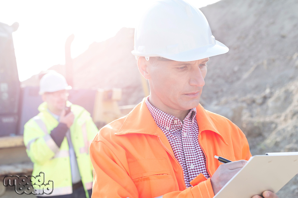 Engineer writing on clipboard at construction site with colleague in background