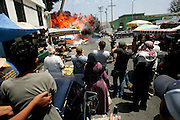 A car explodes as extras and crew members watch the filming of a public service announcement to air on Iraqi television in Los Angeles, California May 20, 2006. The downtown Los Angeles street was turned into Baghdad marketplace being targeted by a suicide bombing.  REUTERS/Max Morse