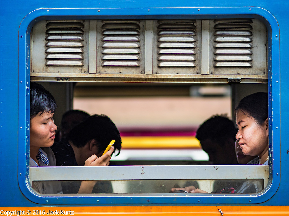 25 JUNE 2016 - BANGKOK, THAILAND:  People on a 3rd class train leaving Hua Lamphong train station in Bangkok for eastern Thailand. Hua Lamphong train station opened on June 25, 1916 after six years' construction. The station was built in an Italian Neo-Renaissance-style, with decorated wooden roofs and stained glass windows. The architecture is attributed to Turin-born Mario Tamagno. There are 14 platforms, 26 ticket booths, and two electric display boards. Hua Lamphong serves over 130 trains and approximately 60,000 passengers each day. Since 2004 the station has been connected by an underground passage to the MRT (Metropolitan Rapid Transit) subway system's Hua Lamphong Station.     PHOTO BY JACK KURTZ