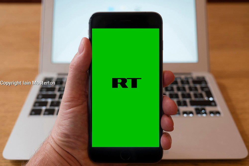 Using iPhone smartphone to display logo of RT, Russia Today, the Russian English language news service