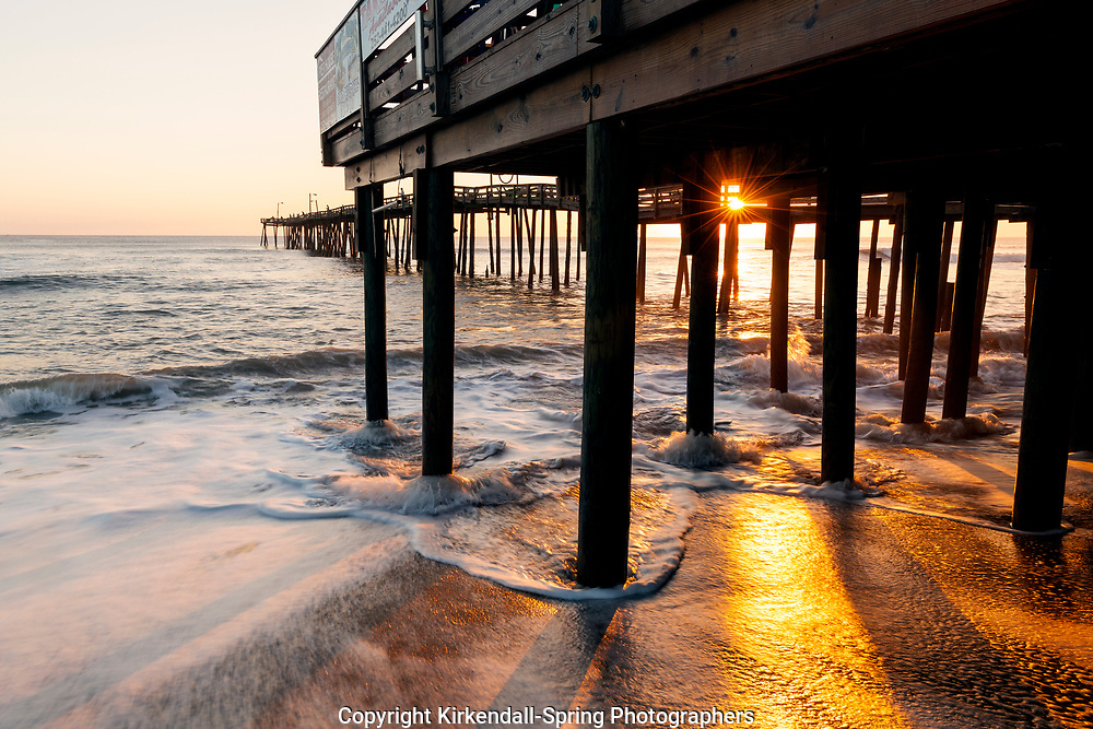 NC00774-00...NORTH CAROLINA - Sunrise and surging tide at the Nags Head Pier on the Outer Banks.