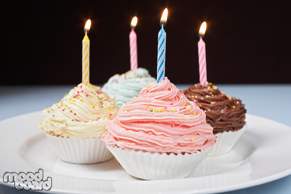 Colourful cupcakes with birthday candles on plate