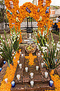 A gravesite decorated with marigolds, candy and fruit for the Day of the Dead festival October 31, 2017 in Tzintzuntzan, Michoacan, Mexico.
