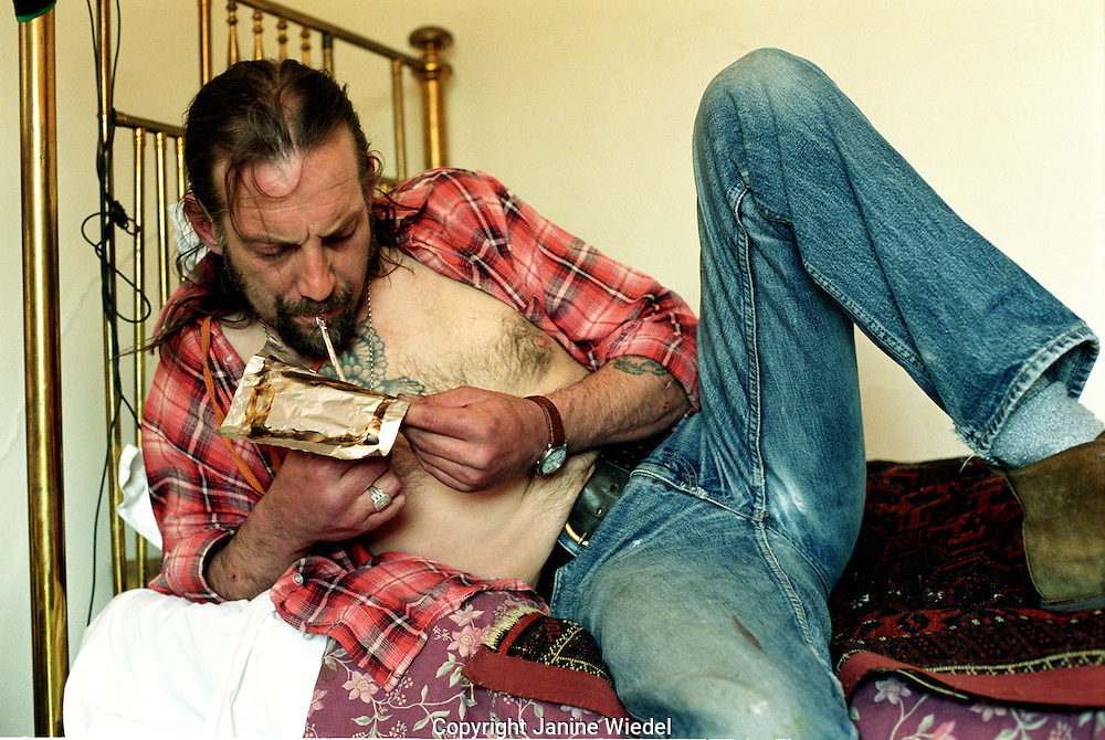 Heroin addict in his bedroom preparing to inject.