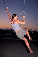Athletic woman excersises by swinging on rings in evening at Santa Monica Beach, Santa Monica, California