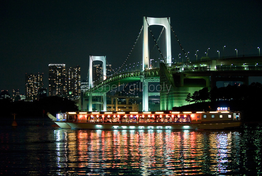 """The lights of a """"yakata-bune"""" pleasure boat are reflected in the calm waters of Tokyo Bay as it prepares to make a turn under Rainbow Bridge in Tokyo, Japan on 31 August  2010. Photographer: Robert Gilhooly"""
