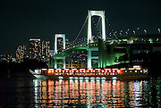 "The lights of a ""yakata-bune"" pleasure boat are reflected in the calm waters of Tokyo Bay as it prepares to make a turn under Rainbow Bridge in Tokyo, Japan on 31 August  2010. Photographer: Robert Gilhooly"