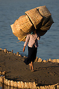 Woman carries woven baskets on her head to deliver, Chindwin River