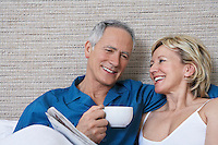 Middle-aged couple in bed smiling