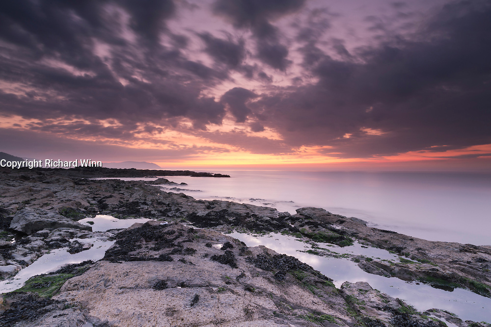 Dusk over Watchet Beach, showing the orange and lilac tones of the sun as it moves further below the horizon, with rockpools in the foreground reflecting the clouds above.