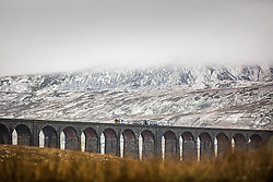 © Licensed to London News Pictures. 23/11/2015. Ribblehead UK. A train travels across the Ribblehead Viaduct in the shadow of the snow covered Whernside mountain as temperatures are expected to warm up today after a freezing weekend. Photo credit: Andrew McCaren/LNP