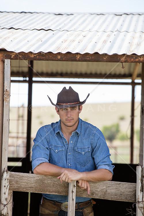 good looking cowboy taking a break in a barn