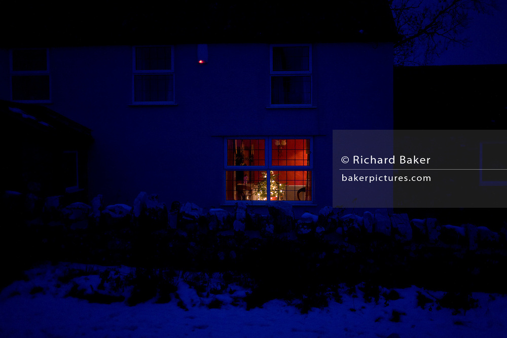 Christmas tree in warmth of rural house seen from outside in bleak temperatures during winter snows in England.