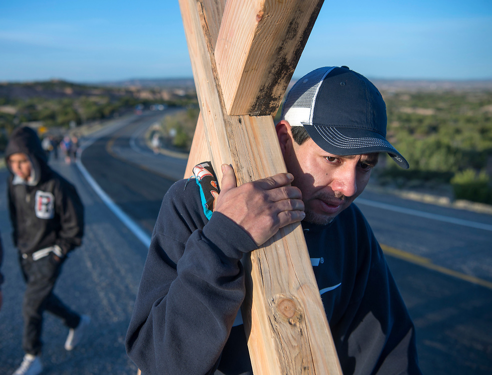 em041417a/a/Francisco Martinez, from Santa Fe, carries a cross along Highway 503 on his way to the Santuario de Chimayo, Friday April 14, 2017. With beautiful weather, thousands of people were making the Good Friday pilgrimage to the Northern New Mexico church.  (Eddie Moore/Albuquerque Journal