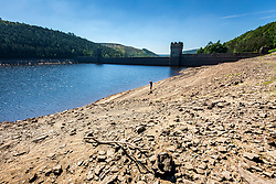 © Licensed to London News Pictures. 05/07/2018. Upper Derwent Valley UK. Scenes this morning at Howden Reservoir in Derbyshire show the extent the water level has dropped during the UK heatwave leaving a sun scorched shoreline. Photo credit: Andrew McCaren/LNP