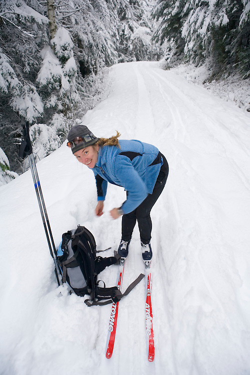 Smiling young female cross country skier on snowy road Mt Baker Snoqualmie National Forest Washington USA.