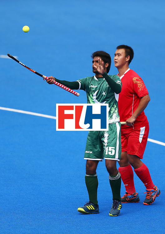 LONDON, ENGLAND - JUNE 25:  Muhammad Dilber of Pakistan attempts to control the ball while under pressure from Wei Wo of China during the 7th/8th place match between Pakistan and China on day nine of the Hero Hockey World League Semi-Final at Lee Valley Hockey and Tennis Centre on June 25, 2017 in London, England.  (Photo by Steve Bardens/Getty Images)
