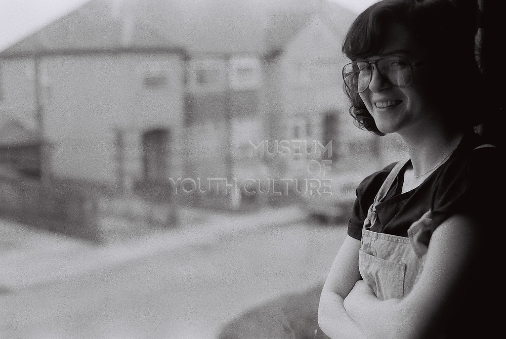 Girl in large glasses standing by a window, Southall, UK, 1985.