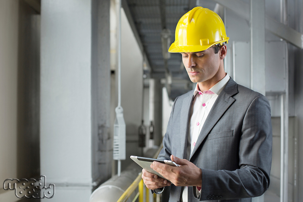 Young male architect using tablet computer in industry