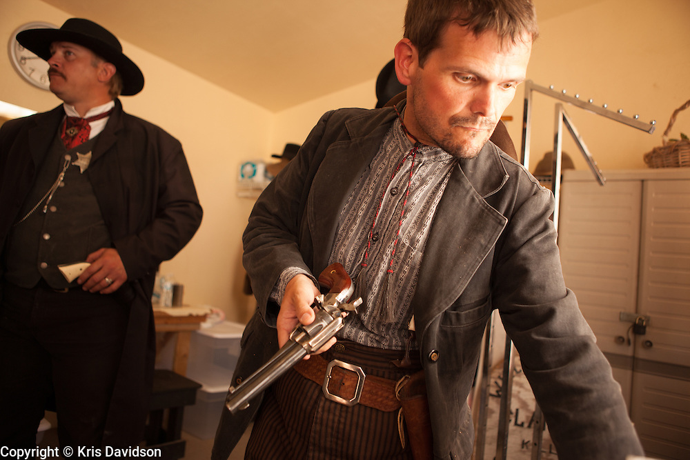 Actors take a break backstage between re-enactments of the infamous gunfight at the OK Corral in Tombstone, Arizona. Tim Fattig leads the group -- pictured here reloading blanks in the guns used in the shootout. Kirk Opperman as Virgil Earp is in the background.