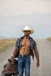 hot muscular cowboy with open shirt holding a saddle on a dirt road