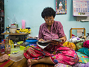 07 APRIL 2016 - BANGKOK, THAILAND: A 79 year old woman who has lived behind the walls at Mahakan Fort her entire life, reads a newspaper in her home. She is facing eviction at the end of April 2016. Mahakan Fort was built in 1783 during the reign of Siamese King Rama I. It was one of 14 fortresses designed to protect Bangkok from foreign invaders, and only of two remaining, the others have been torn down. A community developed in the fort when people started building houses and moving into it during the reign of King Rama V (1868-1910). The land was expropriated by Bangkok city government in 1992, but the people living in the fort refused to move. In 2004 courts ruled against the residents and said the city could take the land. The final eviction notices were posted last week and the residents given until April 30 to move out. After that their homes, some of which are nearly 200 years old, will be destroyed.       PHOTO BY JACK KURTZ