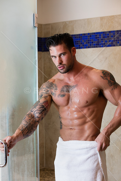 sexy man in a towel standing by a shower