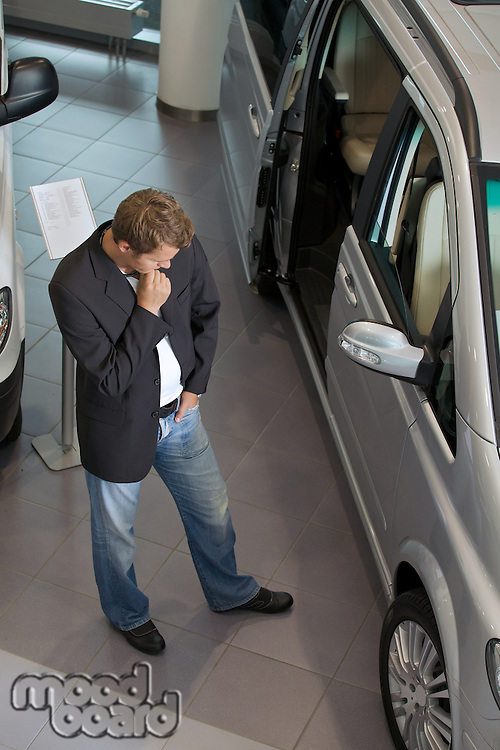 Young man examining new car at showroom