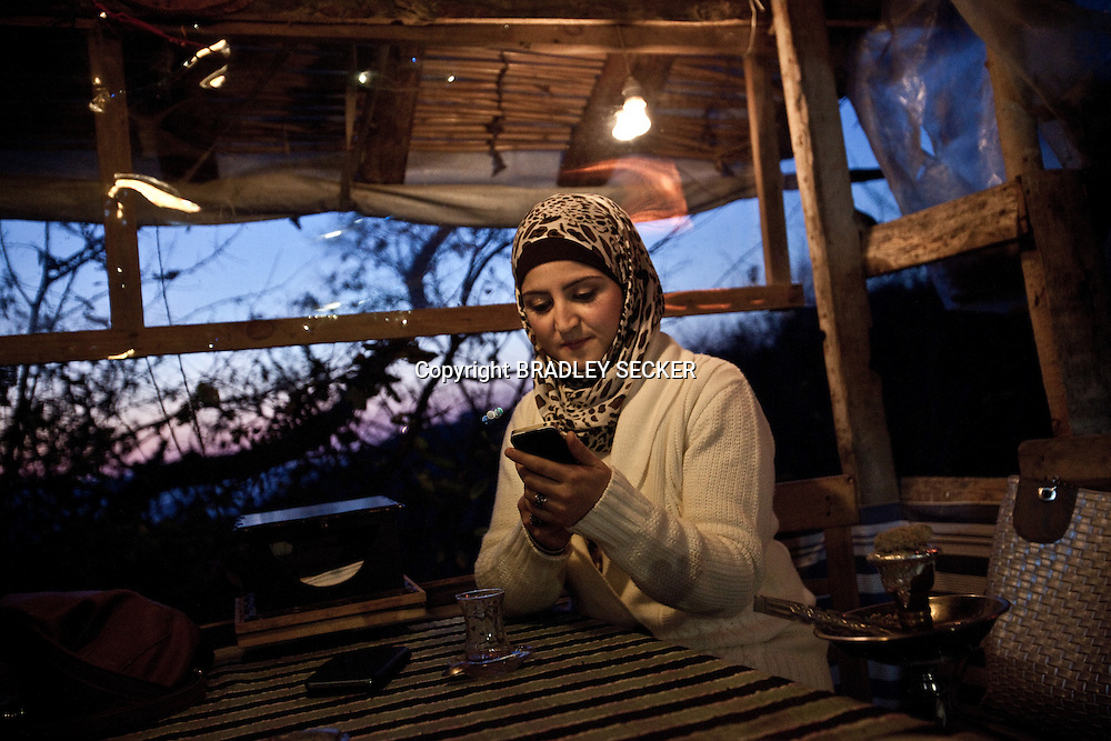 Hiba al Haji, sitting in a cafe on the outskirts of Antakya, close to Turkey's border with Syria. Hiba distributes humanitarian aid and school supplies to displaced Syrians within Syria, and the camp for IDPs in Atmeh. Bradley Secker for the Washington Post. 12/30/2012