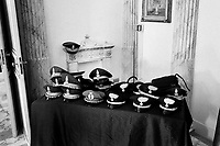 """Palermo, Italy - 20 July, 2012: Hats of the Carabinieri and of the Guardia di Finanza, two of Italy's armed forces, are left at the entrance of a room before a civil gold medal delivery ceremony at Palazzo d'Orléans, the headquarters of the presidency of the Sicilian region in Palermo on 20 July, 2012. <br /> <br /> Mario Monti has expressed """"serious concerns"""" that Sicily's regional government is heading towards default and has asked its governor – who is under investigation for suspected links to the Mafia – to confirm his intention to resign. Sicily was among 23 Italian """"sub-sovereign entities"""" downgraded by Moody's rating agency on Monday, a development that has raised the possibility of a chain of defaults at the local level unless the central government intervenes. Sicily's debt was €5.3bn at the end of 2011, according to Bloomberg. Mr Monti, Italy's technocratic prime minister, indicated in his statement on Tuesday that Rome would take action to bail out Sicily's debts. Sicily has long been identified as one of the most poorly managed of Italy's regions, with the public sector accounting for the bulk of the island's economy and jobs. Commentators call it """"Italy's Greece""""."""