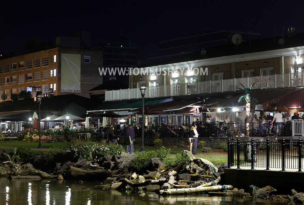 Newburgh, New York - People stand on the sidewalk along the Hudson River waterfront and crowd the bars and restaurants in the background on the evening of June 15, 2011.