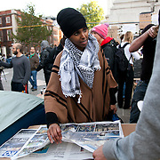 Muna Hassan is looking through news paper coverage of the actions which have taken place all over the world with fellow activists. Day three of the occupation - and the first Monday. The Occupy London Stock Exchange movement was formed in London in solidarity with the US based Occupy Wall Street. The movements are a respons and in anger to what is seen by many as corporate greed and a failed banking system being bailed out by the public, - which in return are suffering austerity measures to make up for the billions of lost money. The movement occupied the St Paul's Square in the City of London Sat Oct 15 after it failed to secure and occupy Pator Noster Square and the Stock Exchnage itself.