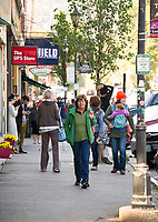 Folks making their way up and down Main Street in downtown Plymouth on Tuesday morning.  (Karen Bobotas/for the Laconia Daily Sun)