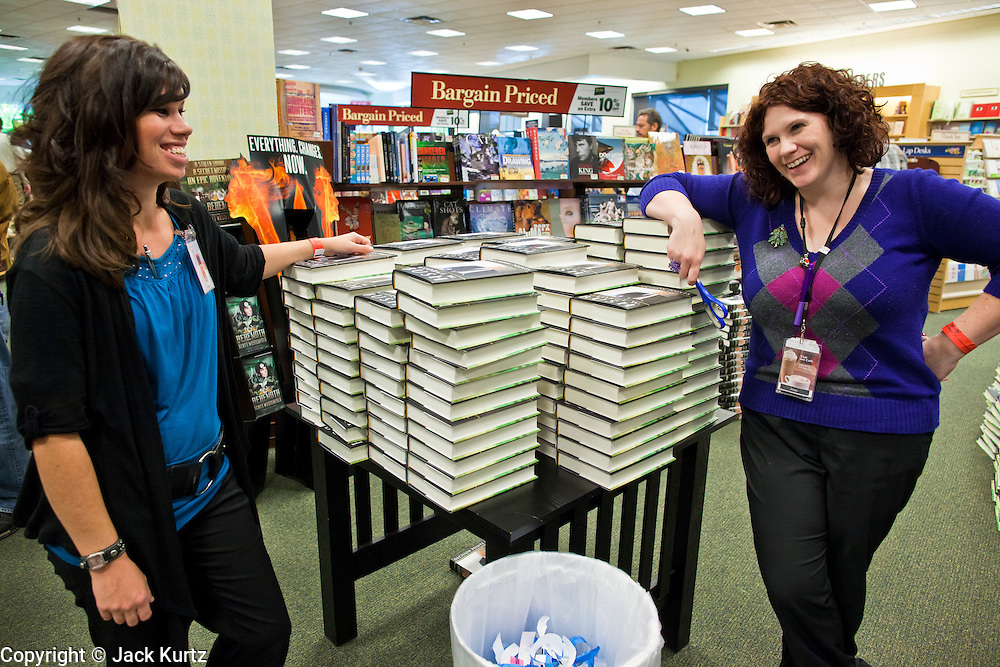 """09 DECEMBER 2010 - PHOENIX, AZ: KATIE RAY (left) and JESSICA MADAGLIA hand out copies of George W. Bush's book, """"Decision Points"""" at the Barnes & Noble Bookstore in Phoenix, AZ, Thursday, Dec. 9. More than 2,000 people lined up starting at 5AM to get copies of the former President's book, """"Decision Points."""" A handful of protesters demonstrated against President Bush near the bookstore, calling him a """"war criminal.""""  PHOTO BY JACK KURTZ"""