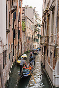 "Gondolas are traditional, flat-bottomed rowing boats which ferry people through Venetian canals. From a peak of 10,000 gondolas 200 years ago, just 500 gondolas now serve Venice. The banana-shaped modern gondola was developed in the 1800s. The left side of a gondola is made longer than the right side to resist leftwards drift at the forward stroke. The gondolier stands on the stern facing the bow and rows just on the right side, with a forward stroke and compensating backward stroke. The oar or rèmo is held in an oar lock, or fórcola, shaped for several rowing positions. The decorative fèrro (meaning iron) ornament on the front can be made of brass, stainless steel, or aluminum, as counterweight for the gondolier standing near the stern. The six horizontal lines and curved top of the ferro represent Venice's six sestieri (districts) and the Doge's cap. Painting gondolas black originated as a sumptuary law eliminating ostentatious competition between nobles. Until the early 1900s, many gondolas had a small cabin (felze) with windows which could be closed with louvered shutters—the original ""venetian blinds."" The romantic ""City of Canals"" stretches across 100+ small islands in the marshy Venetian Lagoon along the Adriatic Sea in northeast Italy, Europe. Venice and the Venetian Lagoons are honored on UNESCO's World Heritage List."