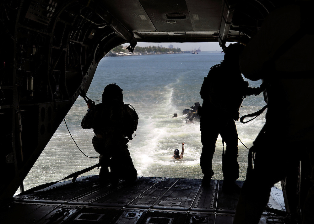 Australian soldiers and others are seen in the water after jumping out of a U.S. Army Chinook helicopter during a drill Wednesday, May 23, 2012.