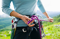 Closeup view of a woman wearing a rock climbing harness and tying into the climbing rope with a figure eight knot.