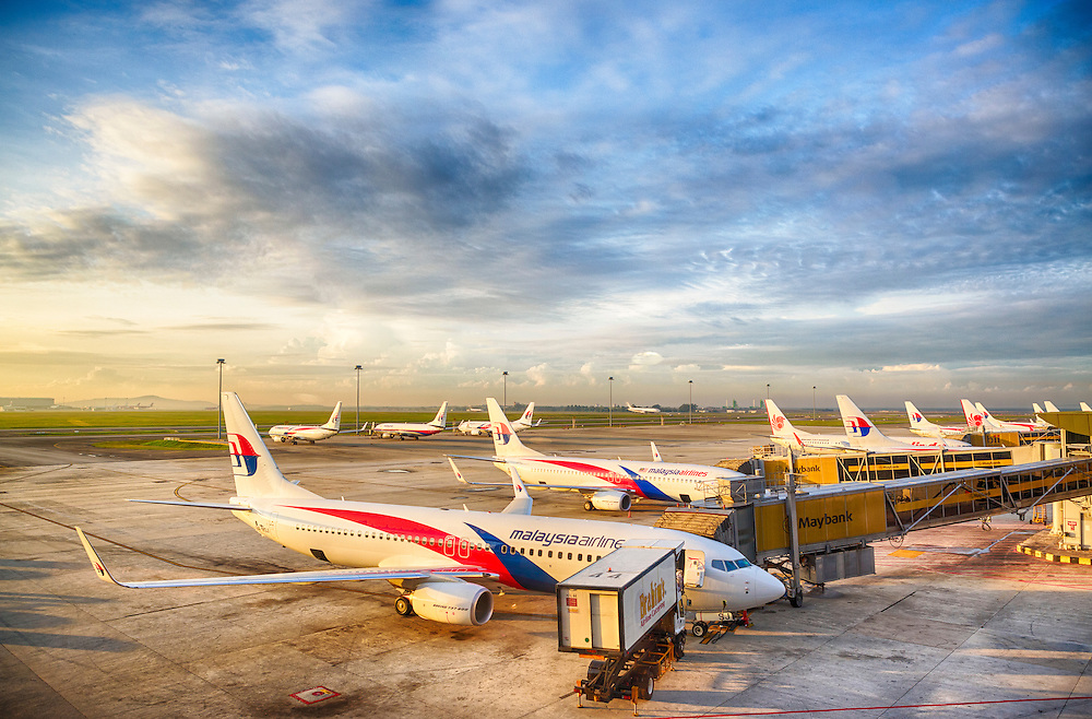 Planes lined up at terminal gates at dawn.