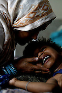 Kaila Sah, a mother of 9, comforts her young child Sunil Kumar as he cries in pain from injuries suffered during an explosion set off in a market by Maoist rebels, at the Disaster ward in the Hospital of the southern Nepali town of Nepalganj Tuesday April 13, 2004. Although more than 600 people have been injured in battles with the police and the street protestors, the five major political parties continue their demonstrations, demanding that King Gyanendra dismiss the government appointed by him, and allow new elections or form a government led by the major parties in the last Parliament.