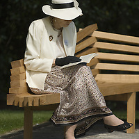 Middle aged elegant woman sitting on a park bench reading<br />