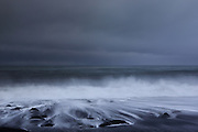 Waves crashing against Reynisfjara beach near Vík in Southern Iceland at dusk.