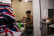 Rosmery preparing breakfast in the kitchen of her home in São Paulo, Brazil, where she lives with her husband, seven children and her grandson.<br /> <br /> Rosmery is Bolivian and moved to Brazil in search of work. Prior to moving in to her own home she lived and worked in a sewing workshop with her family, often for up to 16 hours a day. <br /> <br /> Nowadays she still sews and has long days, but she is based from home.<br /> <br /> Rosmery has received a lot of help and support from Missao Paz who work in partnership with C&A Foundation to  offer advice and support on employment, health, family, community and education.