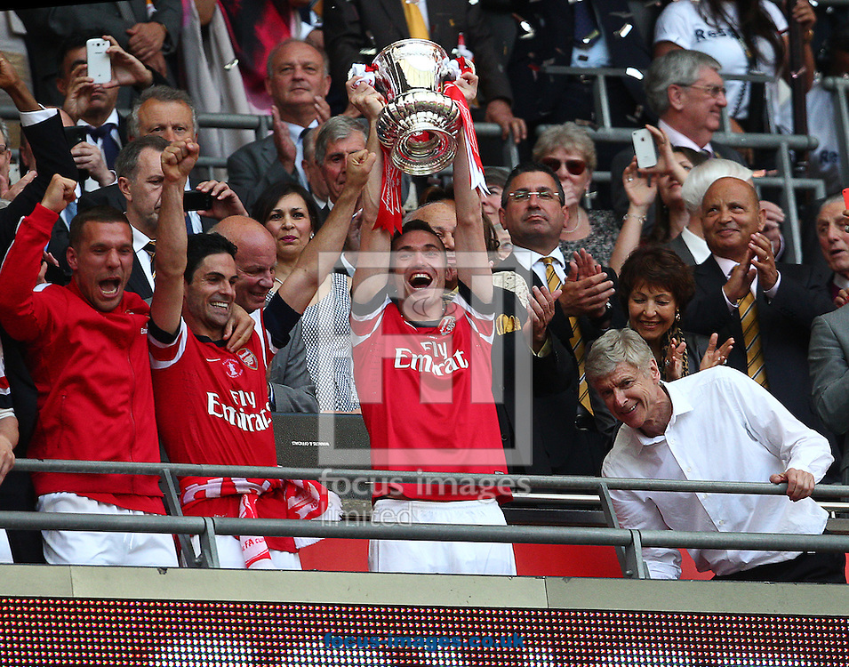 Thomas Vermaelen ( 2ndR ) of Arsenal lifts the FA Cup after his team win during  the The FA Cup Final match at Wembley Stadium, London<br /> Picture by Paul Terry/Focus Images Ltd +44 7545 642257<br /> 17/05/2014