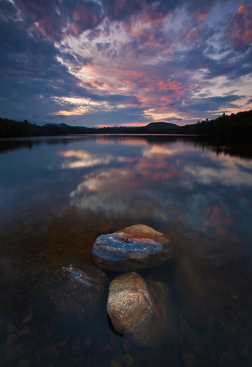 colorful sunset clouds and reflection over Ricker Pond in Groton State Forest, near West Groton, Vermont
