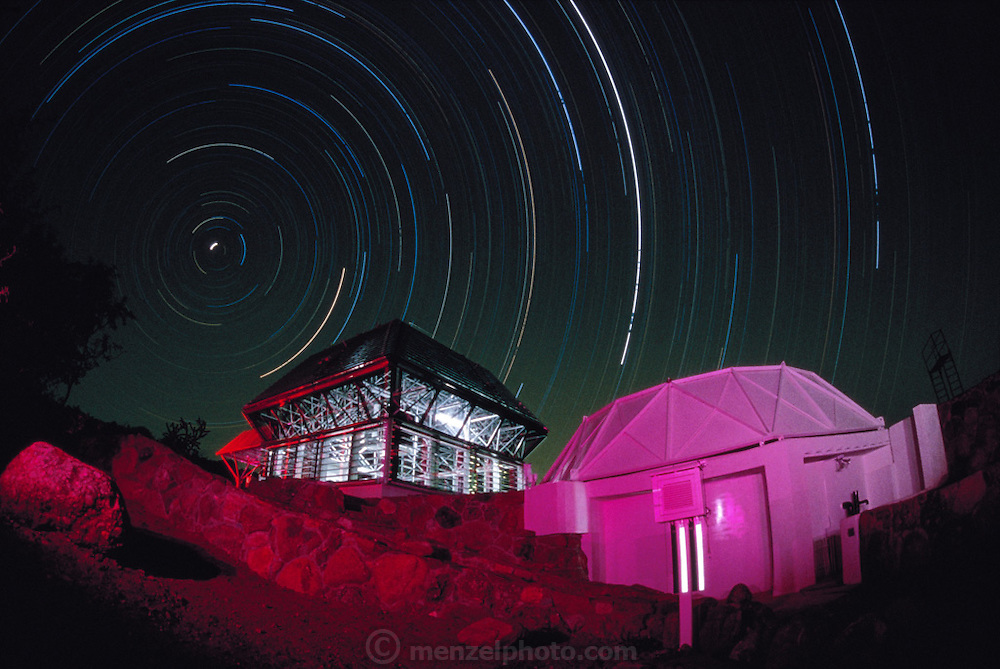 USA_SCI_BIOSPH_78_xs <br /> The Biosphere 2 Project's twenty-seven foot test module seen with star trails at night in a long exposure. The building to the right is an atmospheric chamber used to equalize the air pressure in the module. The Biosphere was a privately funded experiment, designed to investigate the way in which humans interact with a small self-sufficient ecological environment, and to look at the possibility of future planetary colonization. The $30 million Biosphere covers 2.5 acres near Tucson Arizona, and is entirely self-contained. The eight 'Biospherian's' shared their air- and water- tight world with 3,800 species of plant and animal life over their two-year stay in the building, producing all of their own food and supporting the whole environment in five 'biomes'; agricultural, rain forest, savannah, ocean and marsh.  1986