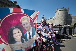 © Licensed to London News Pictures. 15/05/2018. Windsor, UK. Royal fans, who are the first to camp out on the procession route in Windsor High Street, sit amongst flags displaying the faces of the royal couple - ahead of the marriage of Prince Harry and Meghan Markle on Saturday. Photo credit: Peter Macdiarmid/LNP