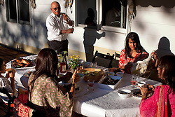 Clockwise from top left, Sonny Massand, niece Abha Gupta, Kiran Massand, daughter Rymn Massand and grandson Aarya Zimmermann have dinner on their porch in Bloomingdale, N.J., Sept. 16, 2011.