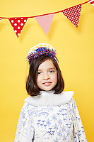 8 year old girl wearing a red white and blue tiara against a yellow seamless.<br /> Photographed at the Photoville Photo Booth September 20, 2015