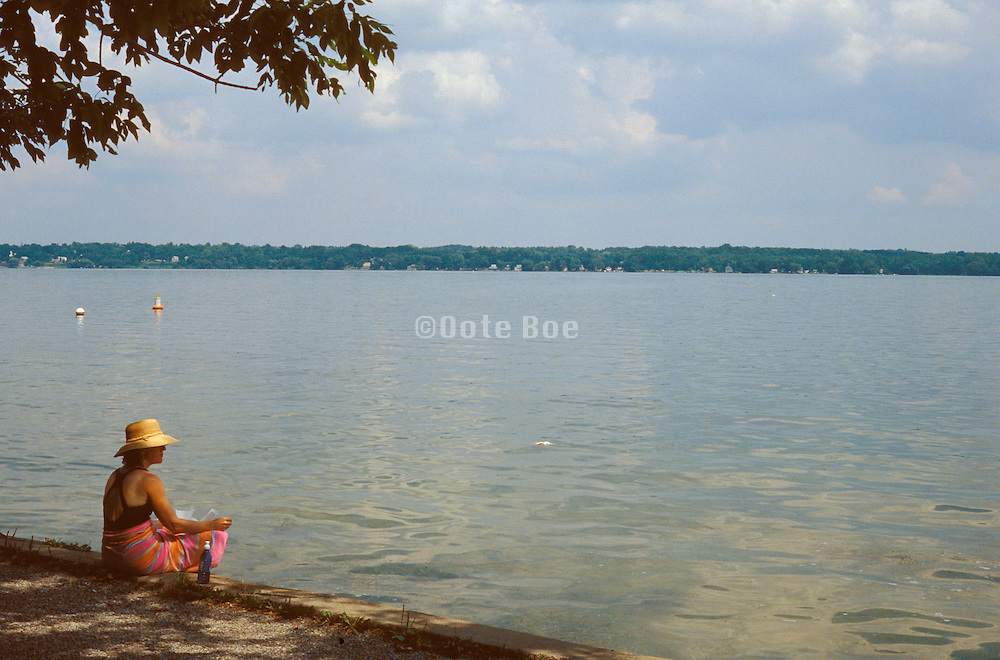 Woman in a straw hat relaxing by the water